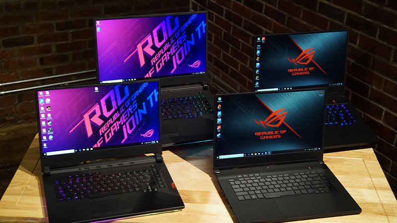 Four opened Republic of Gamers laptops on a table