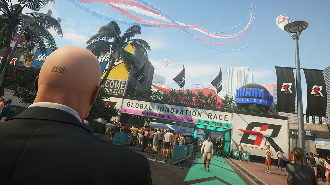 Back view of Agent 47 as he stands in a crowded area at the entrance to a race in Miami