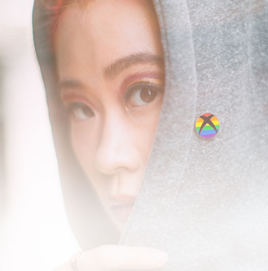 A woman wears an Xbox rainbow pride pin on her grey hoodie