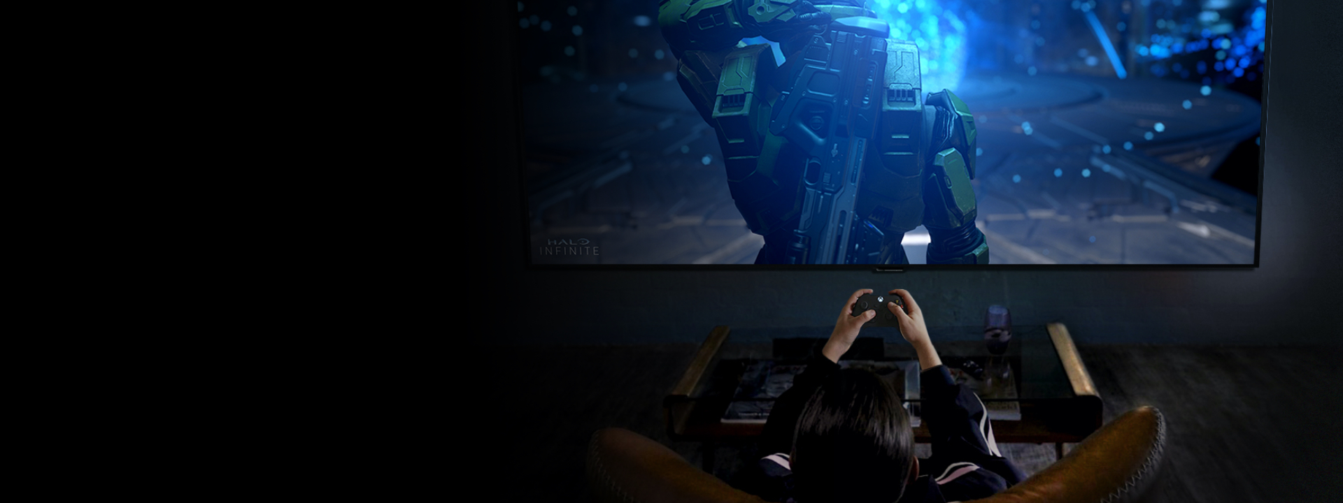 A gamer on a couch playing Halo on an LG OLED TV.