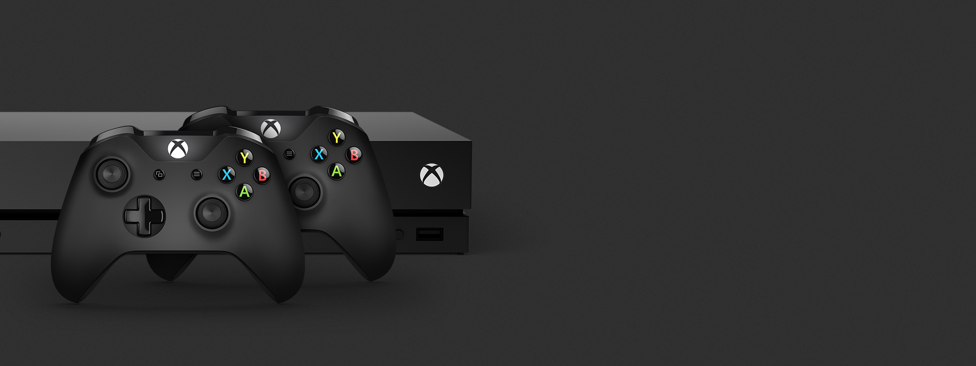 An Xbox One X sits in a dark space with two black Xbox Wireless Controllers