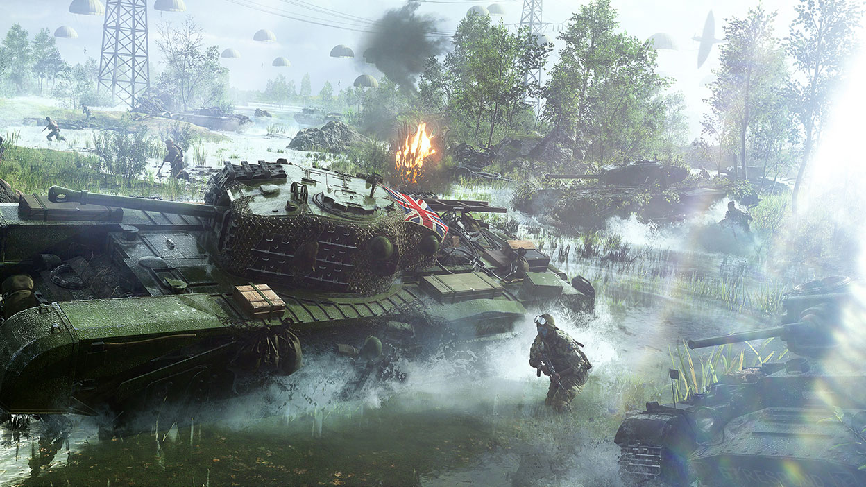 A tank with a British flag on it surrounded by soldiers drives through a swamp.