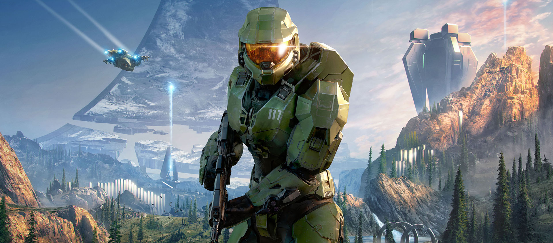 Master Chief stands at the ready, a Halo ring extends into the sky in the distance.