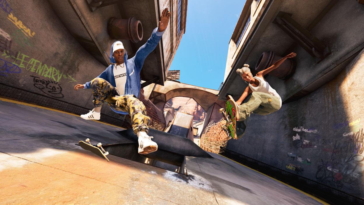 Dos skaters hacen trucos en un callejón vacío.