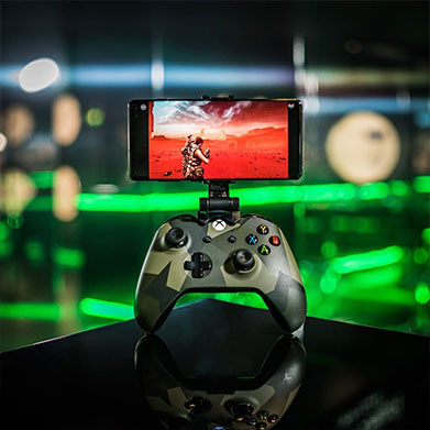 A camo-patterned Xbox One controller with a phone docked on top streaming a game via Project xCloud.