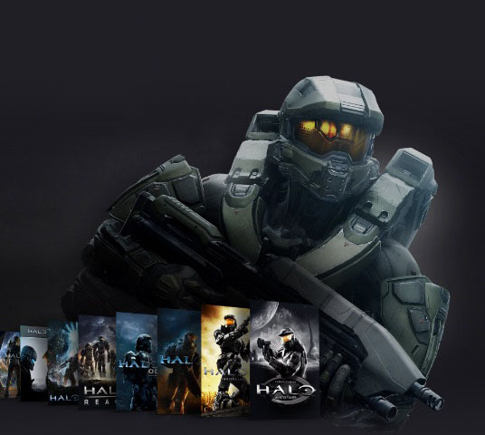 Master Chief stands behind a collection of box shots from the Halo franchise.
