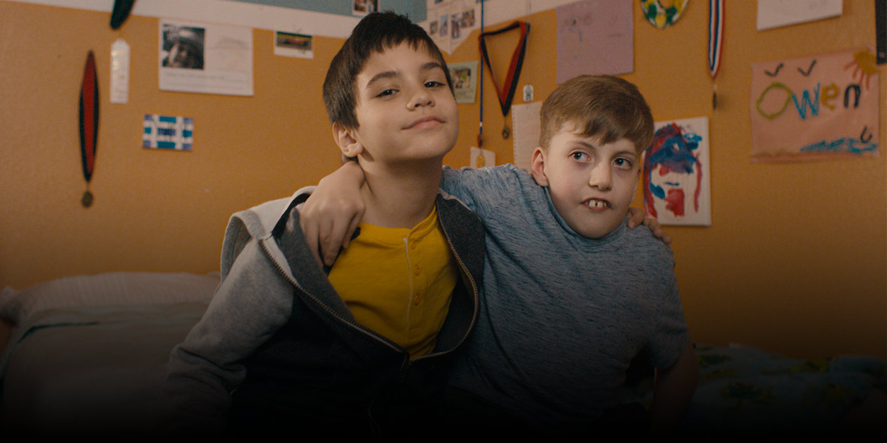Two boys featured in the video hugging and smiling