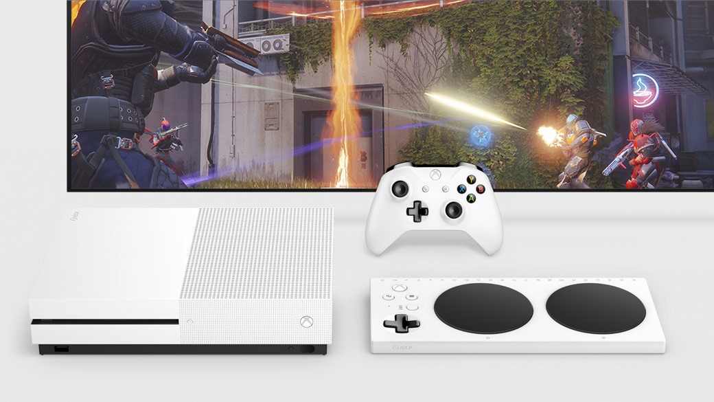 Top down view of the Xbox One S and Xbox Adaptive Controller infront of a TV and a white Xbox Controller