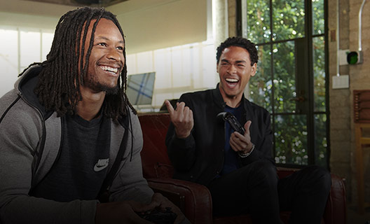 Todd Gurley and host Trey Smith sitting and playing Xbox together