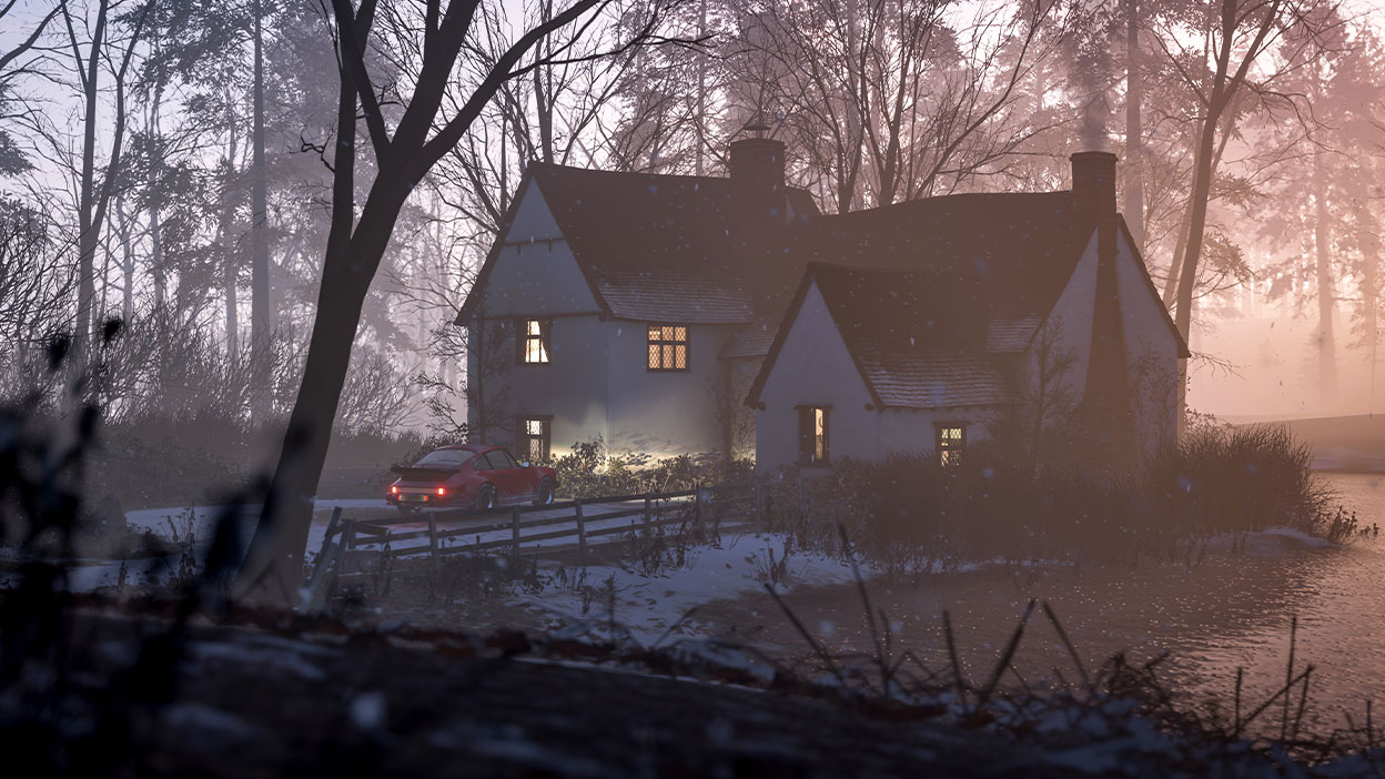 A peaceful lakeside cottage at dusk in the snowfall, lights glowing through the window