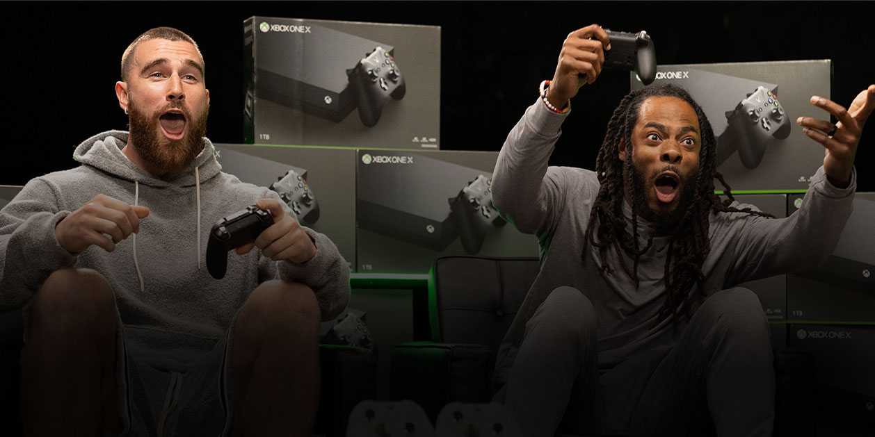 NFL pros Travis Kelce and Richard Sherman react in shock while holding Xbox One controllers.