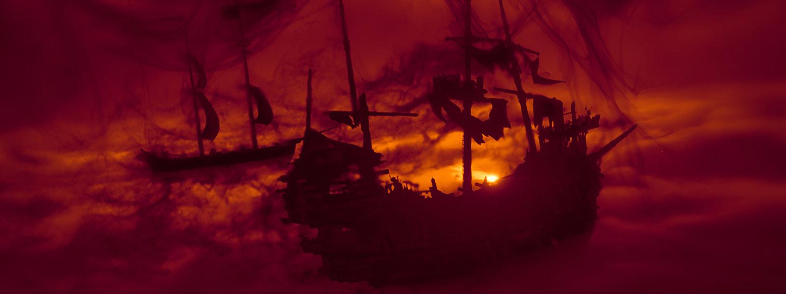 Silueta de dos barcos en el mar, con un fondo rojo