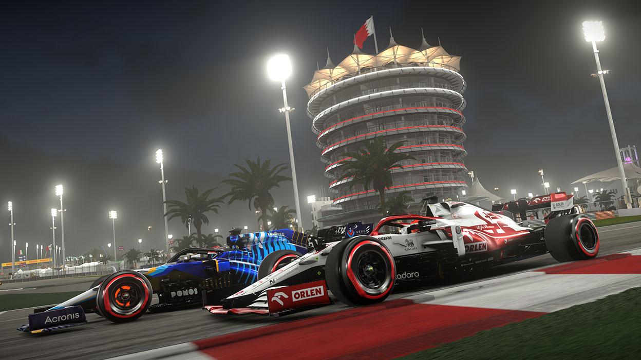 Zwei Autos rasen nachts die Strecke hinunter, mit einem zylindrischen Gebäude in der Ferne.
