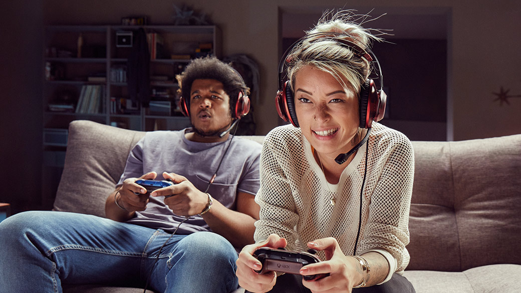 A Man and Woman holding Xbox Controllers playing video games