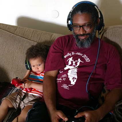 A man and a child sitting on a couch together and playing games, submitted by 'Baid is Born'
