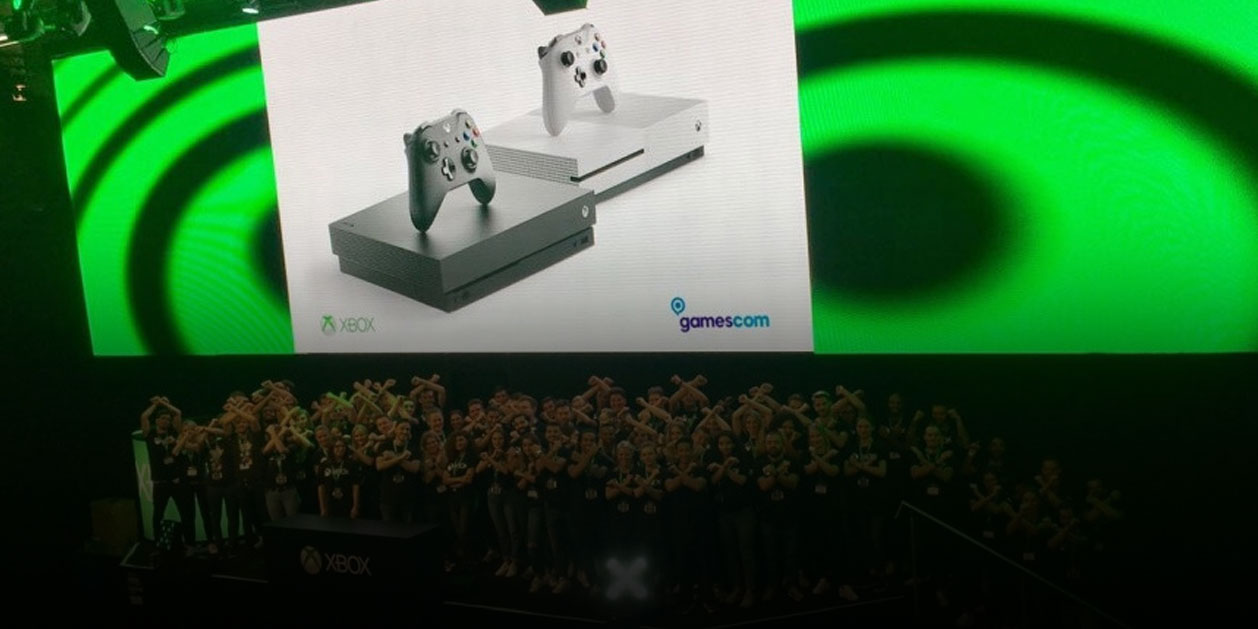 A screen displays two Xbox One consoles above a crowd on stage crossing their arms in Xs