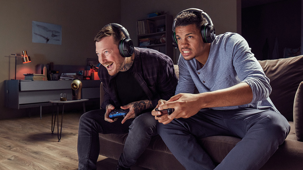 Two men sitting on the same sofa wearing headphones and holding Xbox One controllers.