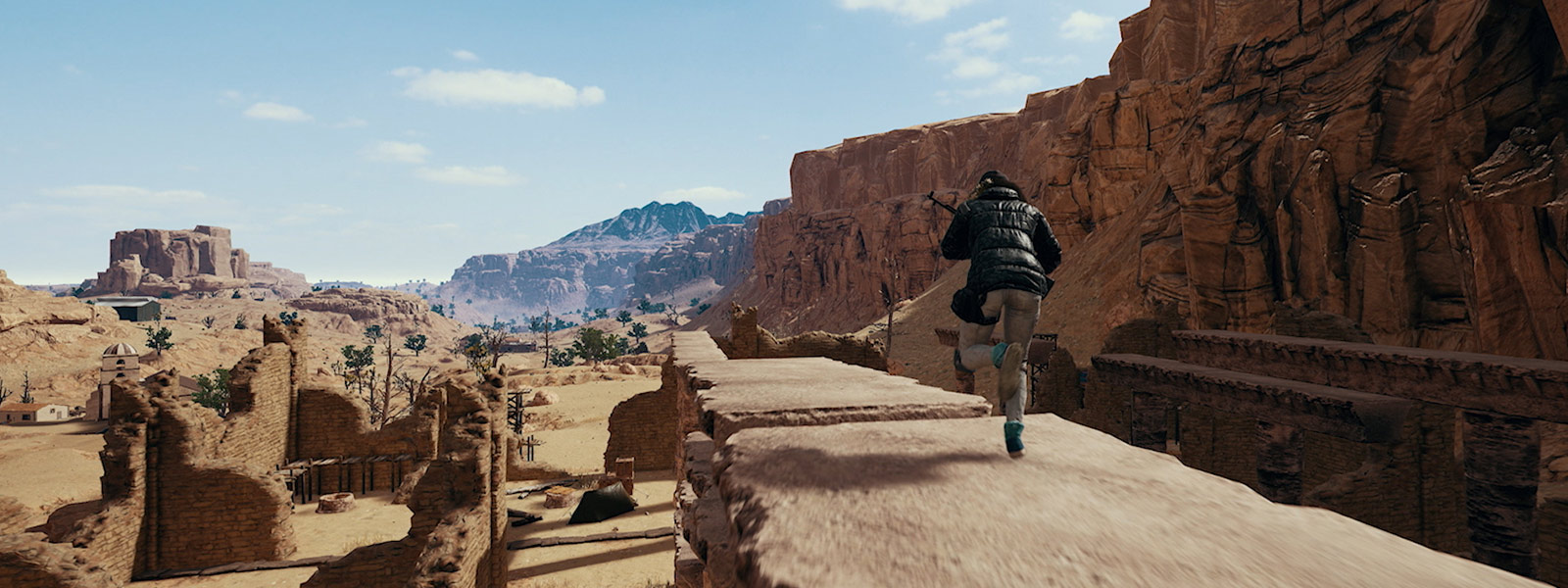 Soldado com rifle correndo através de paredes de tijolos no mapa de Miramar do PLAYERUNKNOWN'S BATTLEGROUNDS