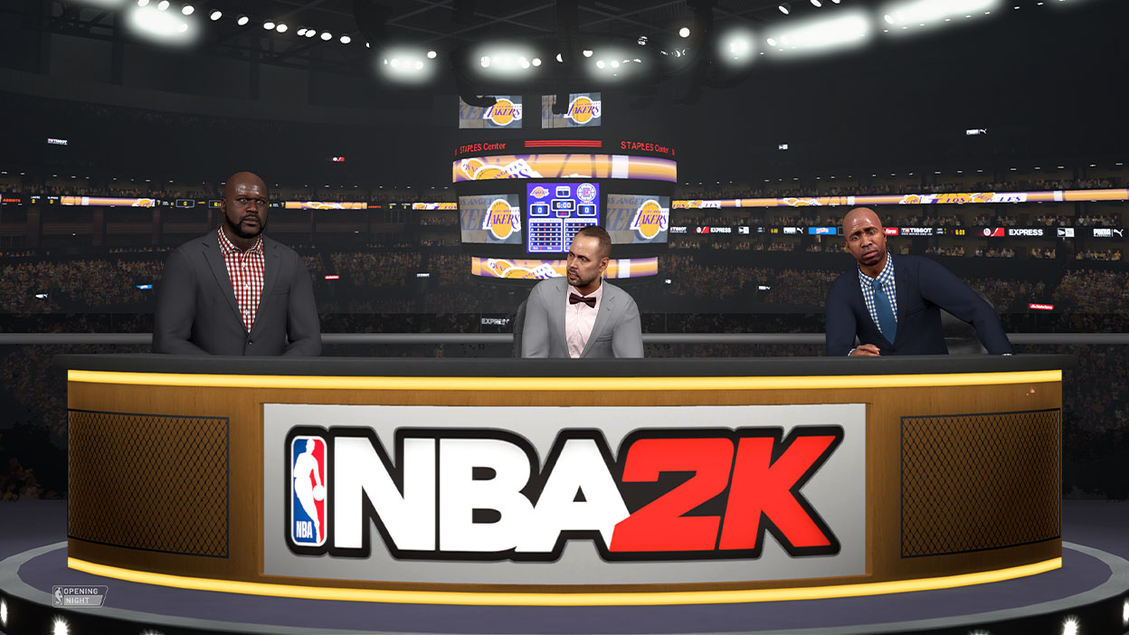 Shaq and two other sportscasters sit behind a NBA 2K analyst desk with the scoreboard behind them in a basketball arena.