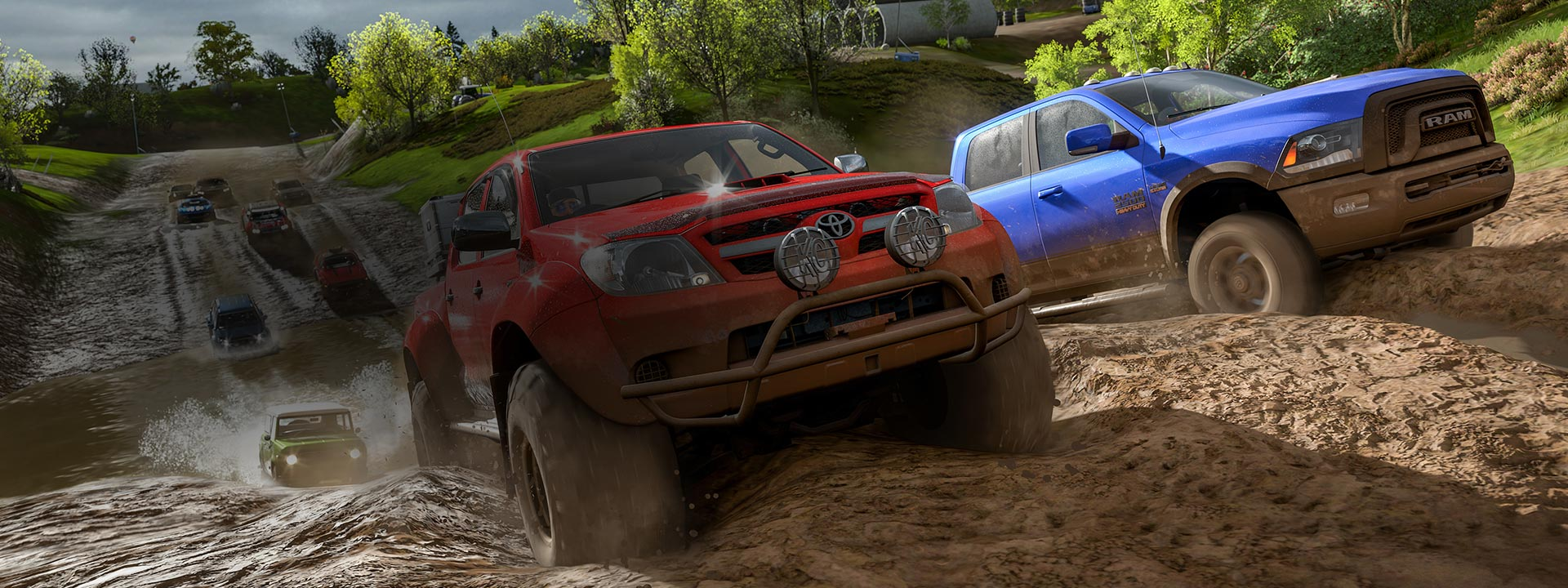 A Toyota pickup and a Dodge Ram cut through a muddy countryside track, in the lead