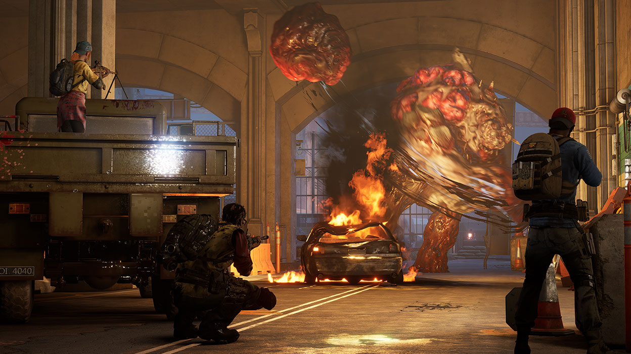 Players battle and shoot a giant zombie monster in a parking garage.