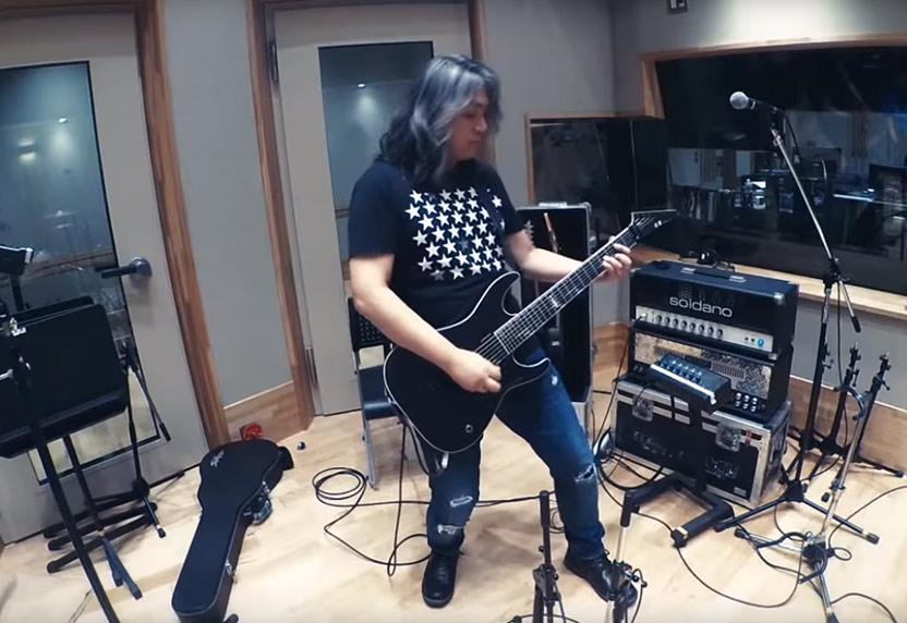 Jun Senoue playing guitar in a music studio