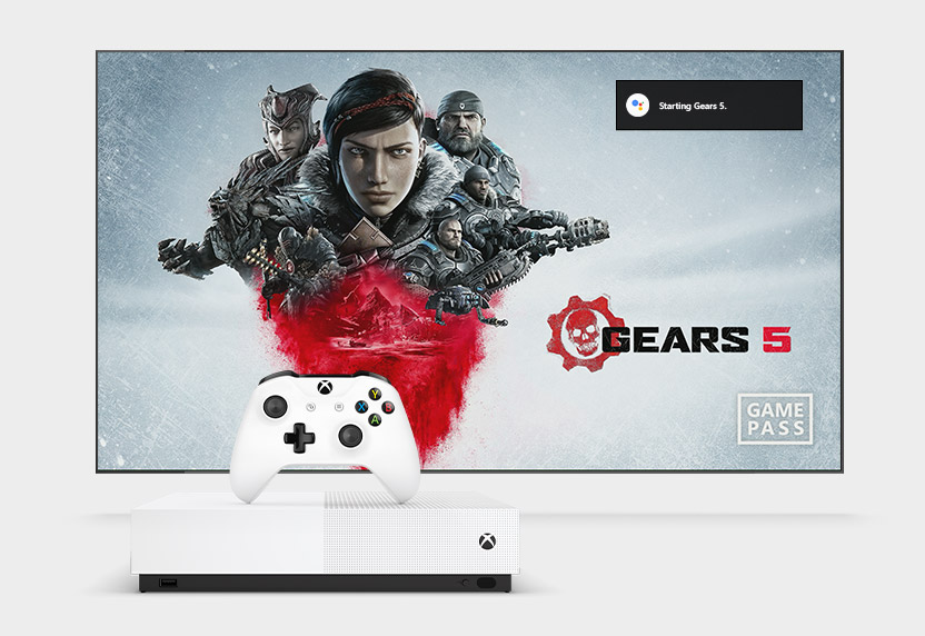 An Xbox One S console and controller sit in front of a TV that is displaying the Gears 5 start screen.