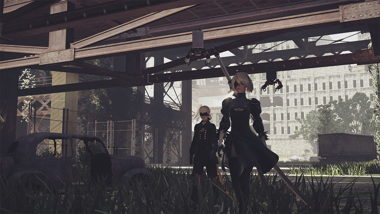 2B and 9S walk under a bridge next to a rundown car