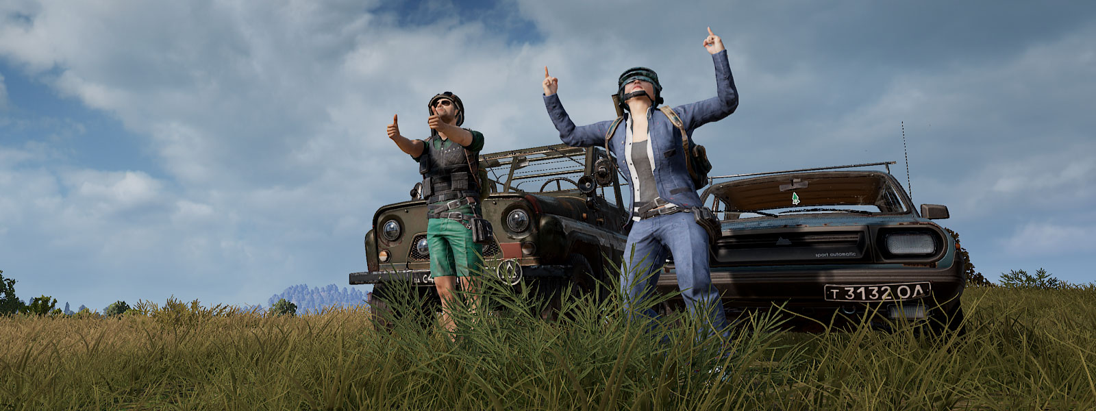 Two players point finger-guns in front of old cars in a field.