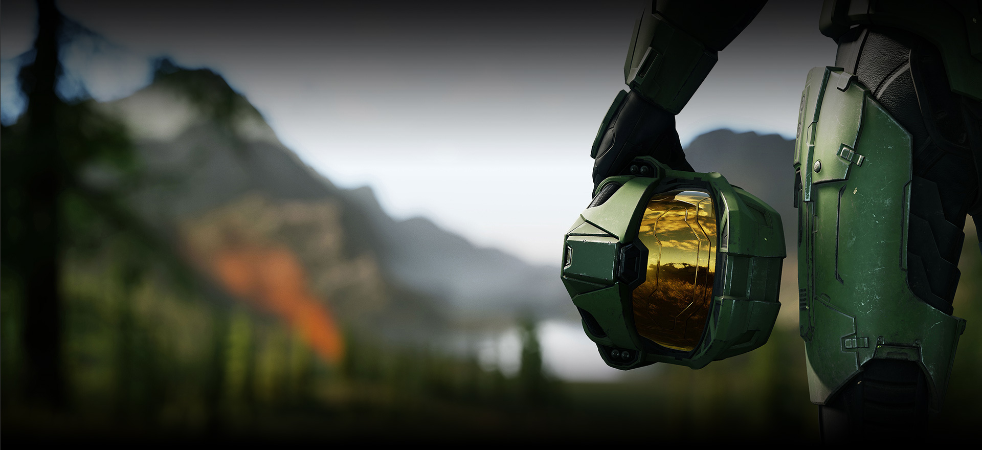 Halo Universe: closeup of Master chief's hand holding his helmet with mountain scene in background.