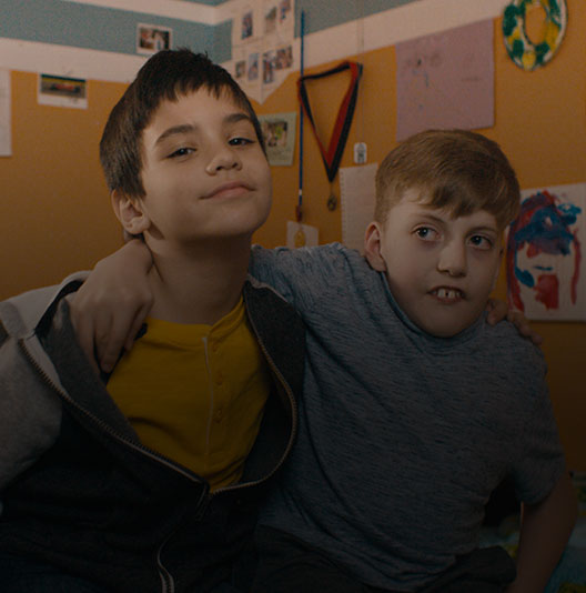 Two boys featured in the accessible gaming for all video hugging and smiling