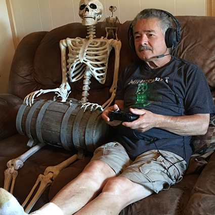 A gamer sitting on a couch next to several skeletal figures, submitted by 'Chocmoojoo'