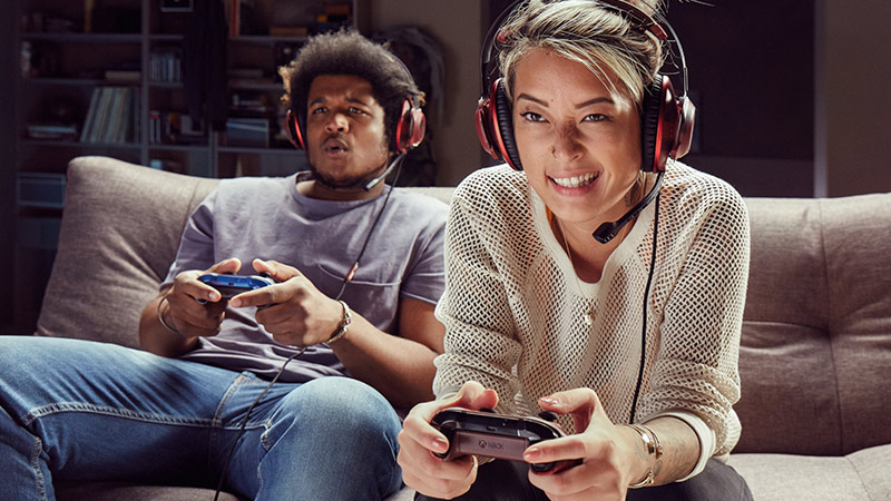 A guy and a girl sitting on a couch playing Xbox Live