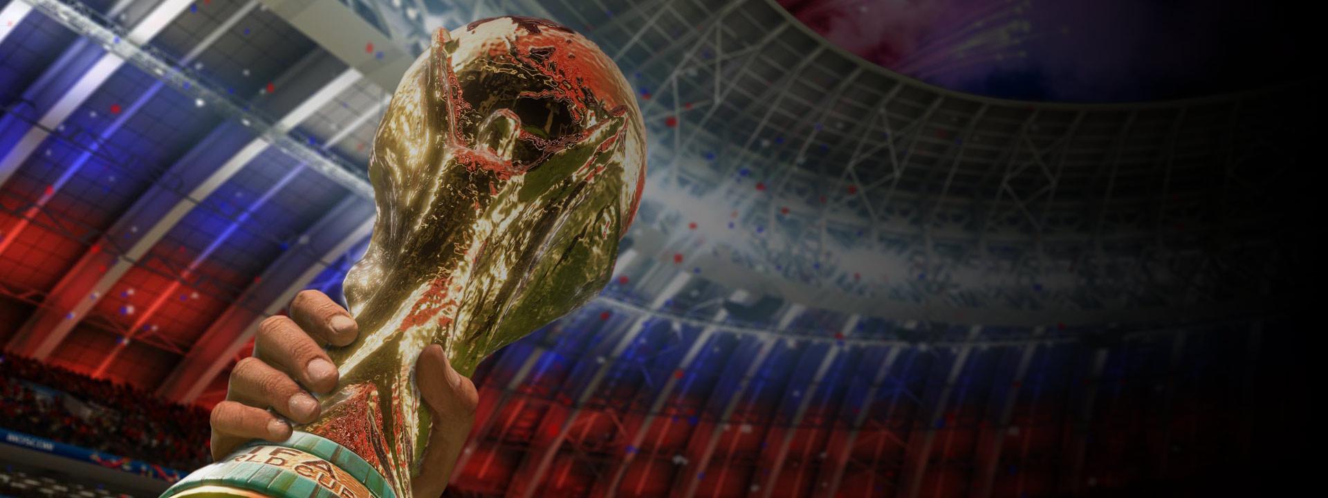 Vista de uma mão levantando a taça da Copa do Mundo da FIFA de 2018 com confetes caindo em um estádio ao fundo