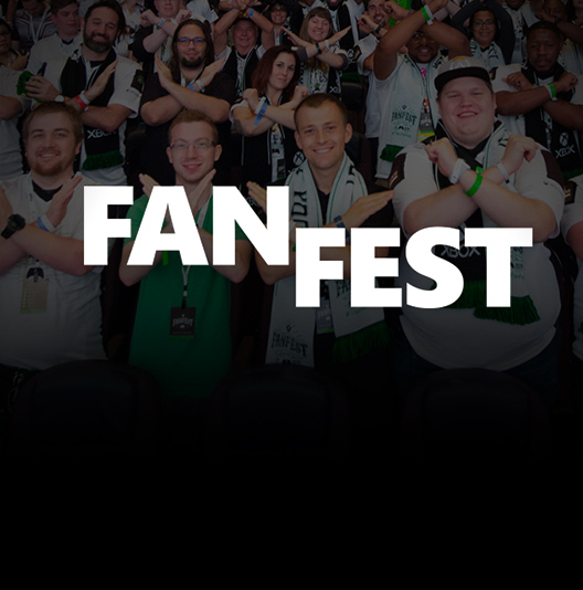 A crowd of Xbox fans form X's with their forearms at Xbox FanFest.